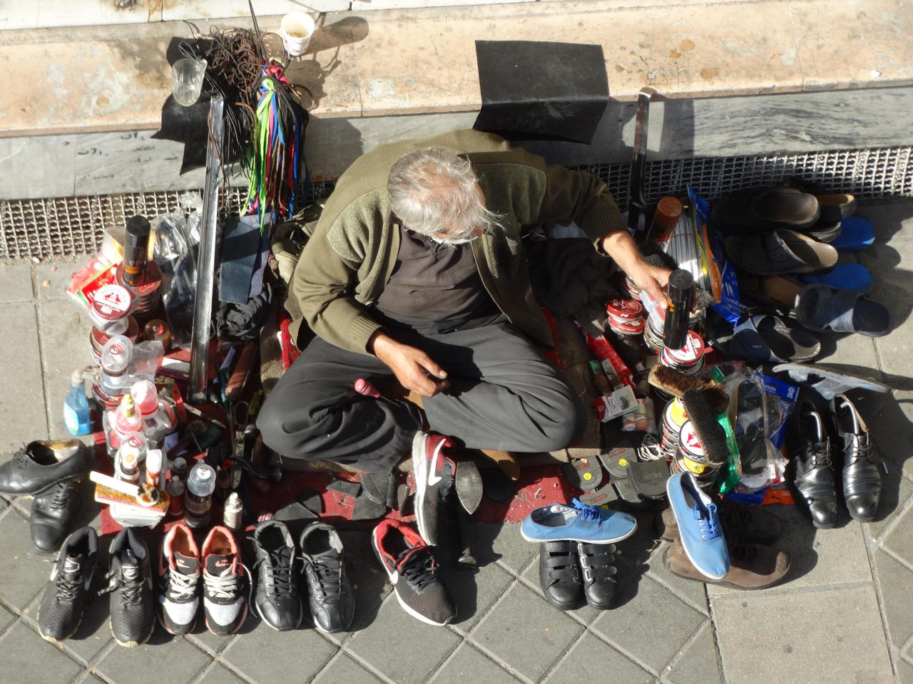 Recession hits shining An old shoe repair man has no customer because of deep economy crisis caused