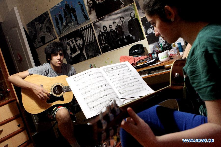 Golnar, 15, and her brother Arjang, 17, practice guitar at their room in Rasht city, northern Iran,