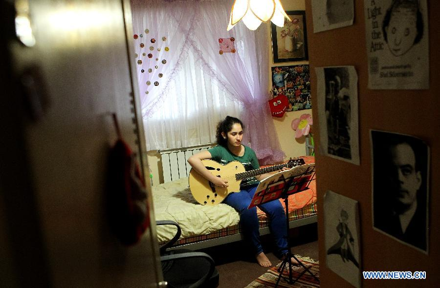 Golnar, 15, practices guitar at the room in Rasht city, northern Iran, on March 2, 2013. Playing Gui